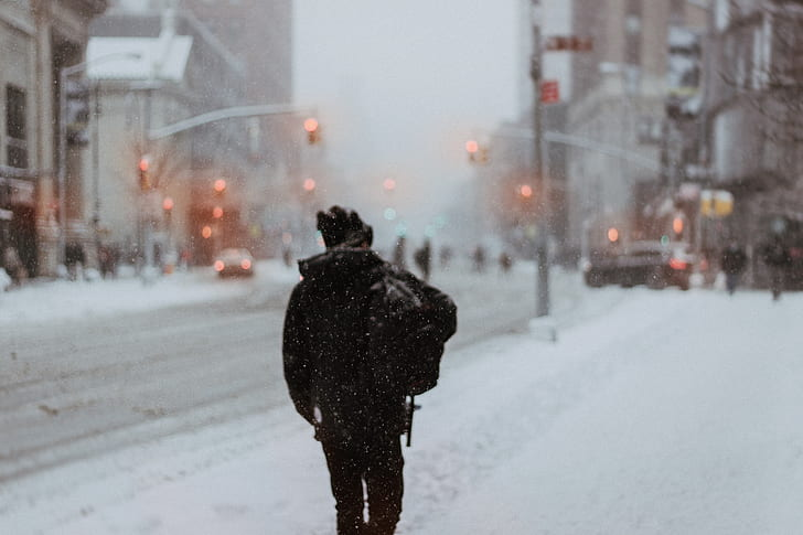 A lone figure on an snow-covered city road.