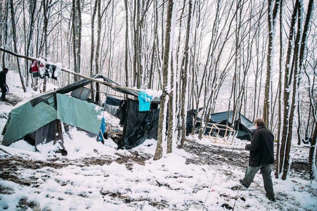 German doctor at makeshift camp in the forest where refugees and migrants live plastic tents in the snow.