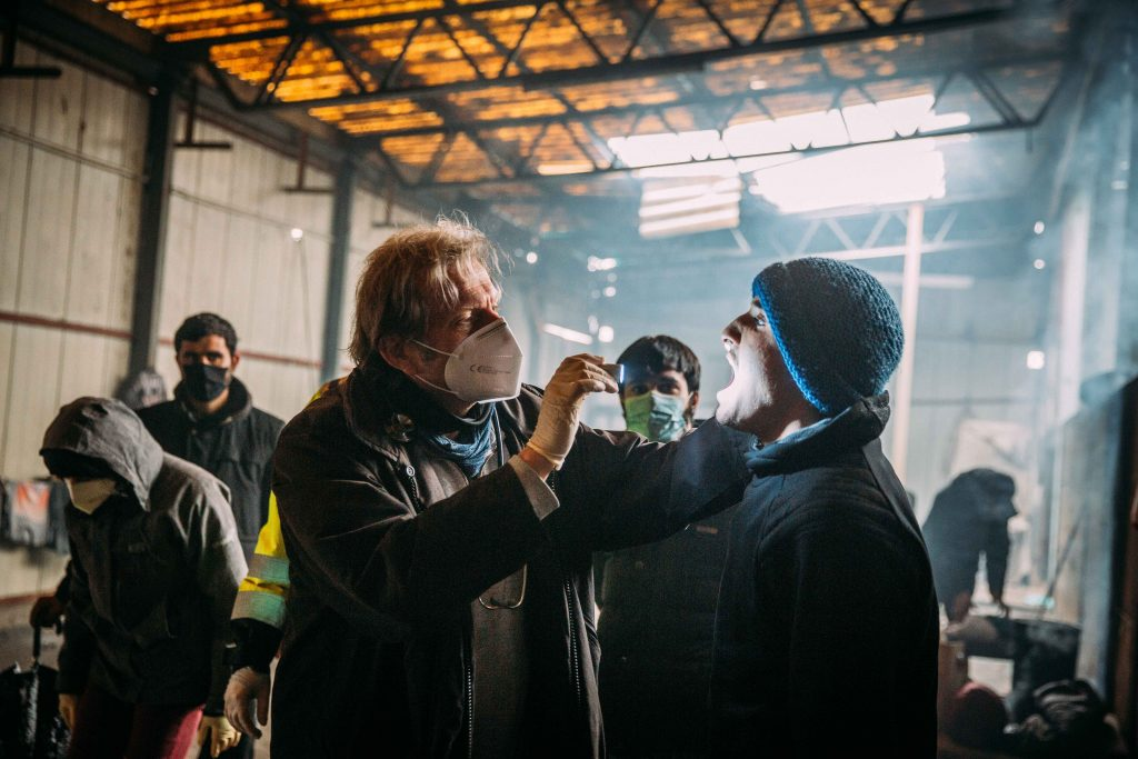 German doctor in abandoned building treating refugees and migrants. Respiratory issues, scabies, wounds.