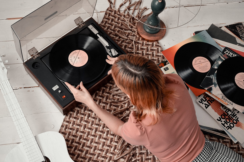 young woman laid down listening placing a vinyl record in a record player